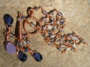 A pile of lariat necklace, copper wire with quartz and glass drops and beads, jewelry by Danielle Rose